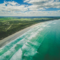 Aerial view of beautiful ocean coastline, white sandy beach, and farm lands in Australia