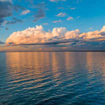 Sunset at ocean coastline - clouds over calm bay waters