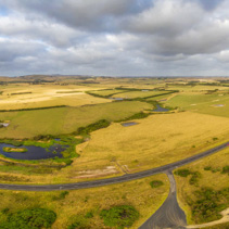 Aerial scenic panorama of rural road passing through pastures and meadows in Australia