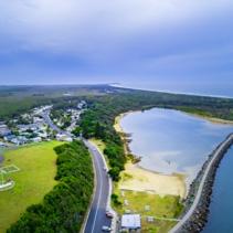 Aerial view of Harrington village, breakwater, and ocean coastline. Harrington, New South Wales, Australia