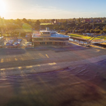 Aerial view of Frankston Yacht Club and footbridge over Kananook creek at sunrise. Melbourne, Victoria, Australia