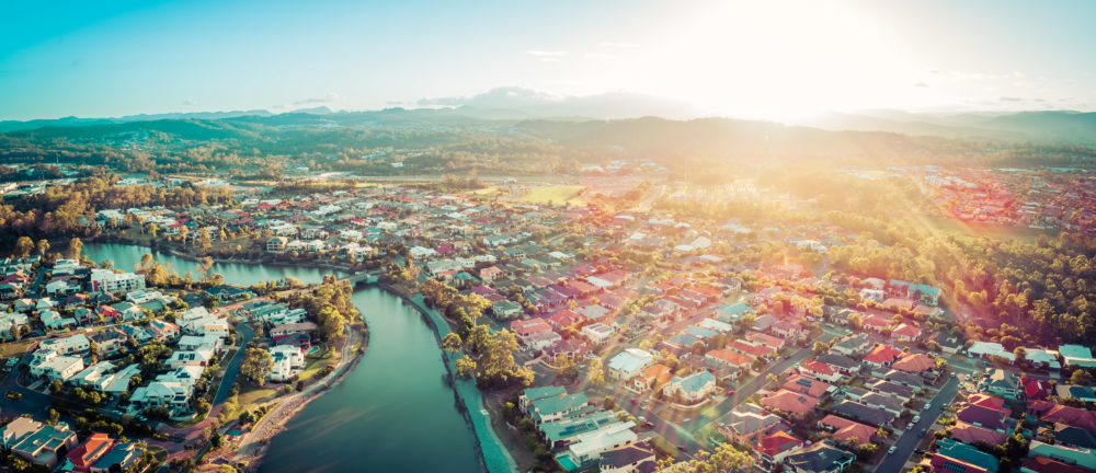 Aerial panorama of beautiful sunset with sun flare over luxury suburb on the Gold Coast, Queensland, Australia