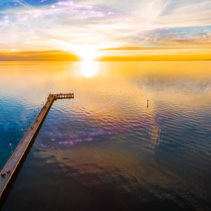 Fantasy landscape - people watching beautiful sunset over sea on pier with planet and galaxy in the sky reflecting in still water. Elements of this image are furnished by NASA