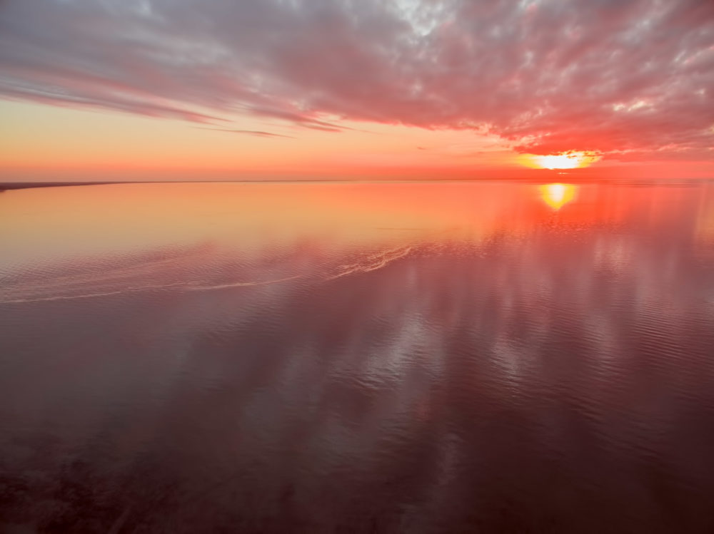 Aerial view of vivid red and orange sunset high above ocean. Nothing but water, sun, and sky