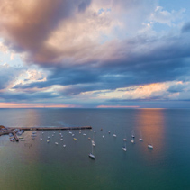 Aerial panorama of cloudscape over long pier and moored boats at sunset