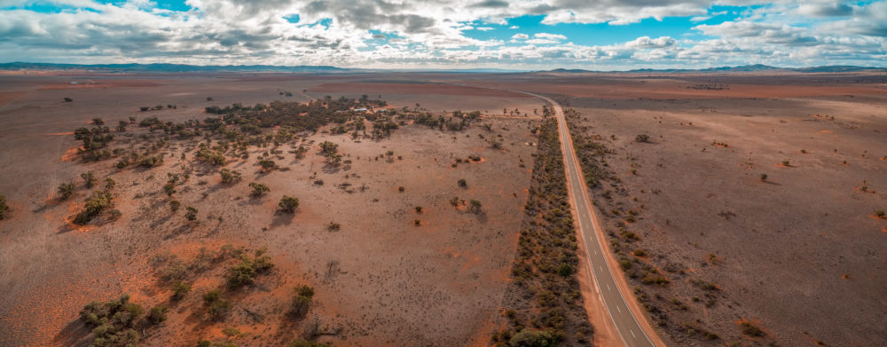 Aerial panorama of rural highway passing through vast plains in Australian outback