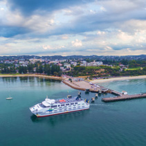 Melbourne, Australia - March 26, 2017: Passenger and car ferry arriving at Sorrento Pier at dawn on Mornington Peninsula. Aerial panoramic view