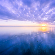 Aerial view of beautiful sunrise - lonely boat in the vast ocean. Nothing but sky, boat and water