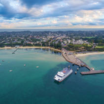 Aerial landscape view of Passenger and car ferry approaching the pier in Sorrento suburb. Mornington Peninsula, Melbourne, Australia