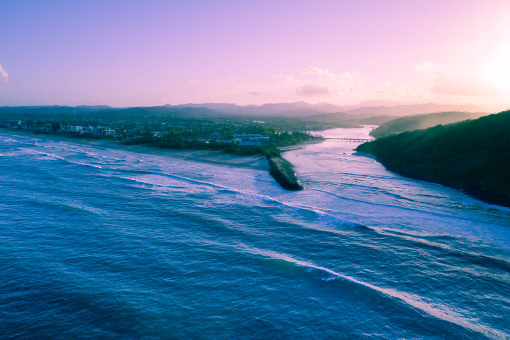 Aerial view of Tallebudgera creek mouth and ocean coastline at sunset. Gold Coast, Queensland, Australia