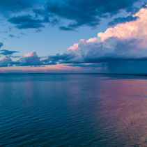 Rain and stormy clouds approaching the ocean coastline and beautiful sunset - aerial view