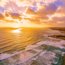 Vivid glowing sunset over ocean and coastline in Australia - aerial landscape