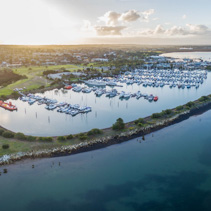Aerial view of Westernport Marina with moored boats and Hastings coastline at beautiful sunset. Melbourne, Victoria, Australia