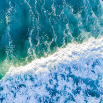 Looking down at powerful blue wave in the sea - aerial view