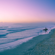 Surfer with surfboard silhouette walking on ocean beach into the water at sunrise