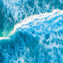 Vivid blue crushing wave at sunset. Aerial view with copy space