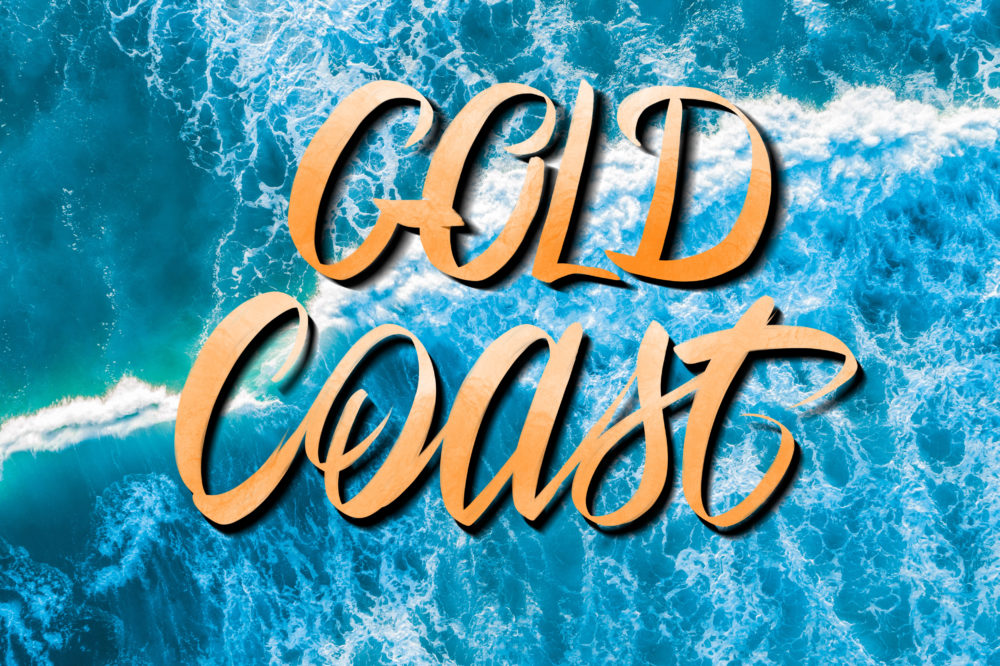 Gold Coast lettering over vivid blue crushing waves