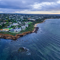 Aerial view of luxury houses on Mornington Peninsula coastline at sunset