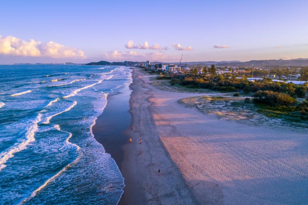 Aerial landscape of Palm Beach suburb coastline at sunset. People walking on the beach. Gold Coast, Queensland, Australia