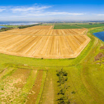 Aerial panorama of Werribee river, plowed field, and Western water treatment plant. Cocoroc, Victoria, Australia
