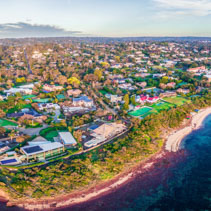 Large aerial panorama of coastline with luxury villas and suburban area at sunset