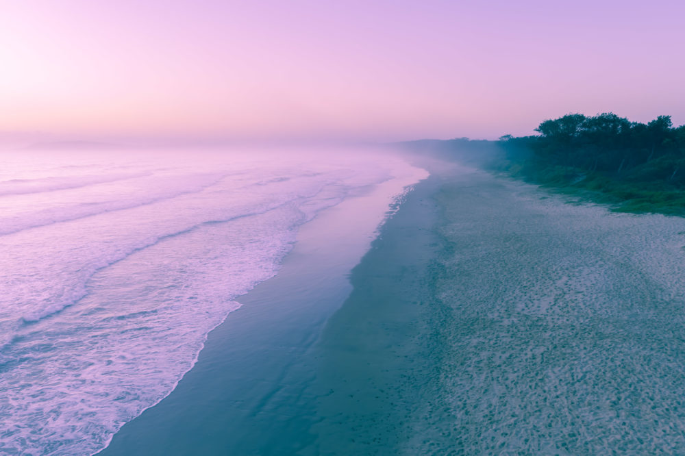 Beautiful vivid misty sunrise at ocean beach - aerial view with copy space