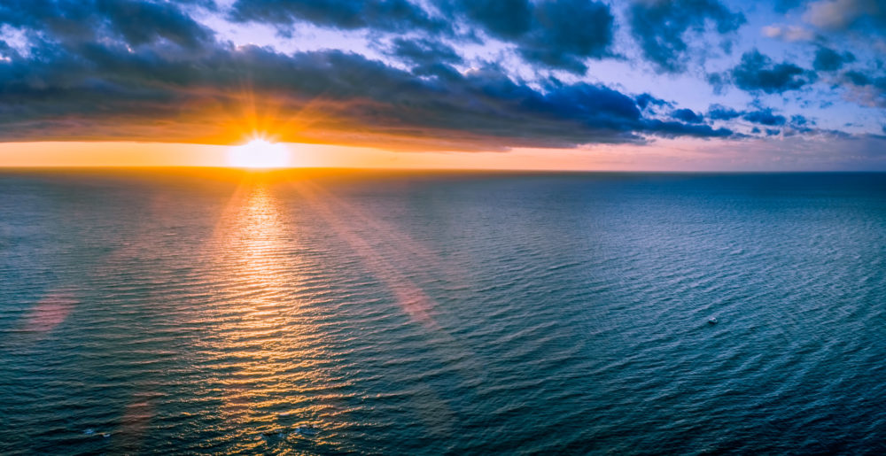 Lonely boat in wast ocean at sunset - wide aerial panorama
