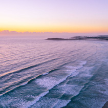 Aerial landscape of sunrise over ocean coastline near Arrawarra, New South Wales, Australia