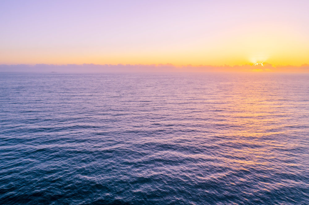 Beautiful minimalist seascape - sunset over water with copy space