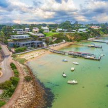 Aerial panoramic landscape of Sorrento suburb coastline with private piers and moored boats. Mornington Peninsula, Melbourne, Australia