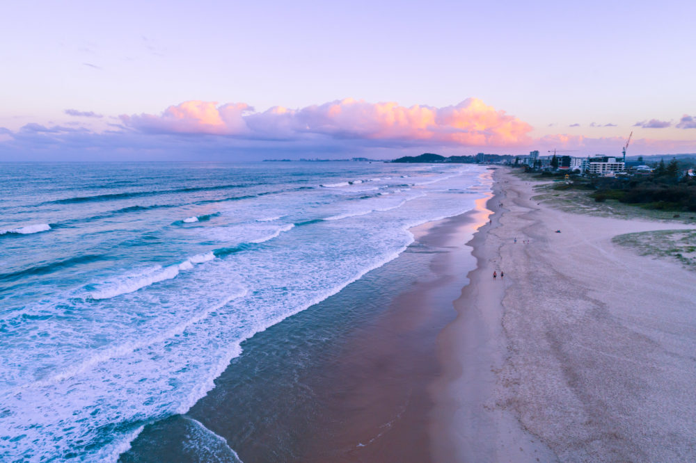 People walking on the beach at sunset - aerial view. Gold Coast, Queensland, Australia