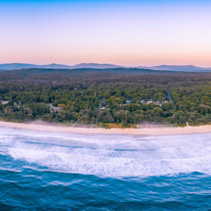Aerial panorama of ocean waves washing up the coastline and coastal vegetation with mountains in the background in the morning with copy space