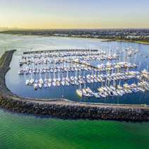 Beautiful aerial view of Yachts moored at marina in Melbourne with CBD skyscrapers visible in the distance at sunset. Melbourne, Victoria, Australia