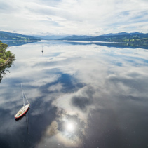 Moored sailboats on Huon River, Huon Valley, Tasmania, Australia. Beautiful aerial image with clouds reflecting in the water