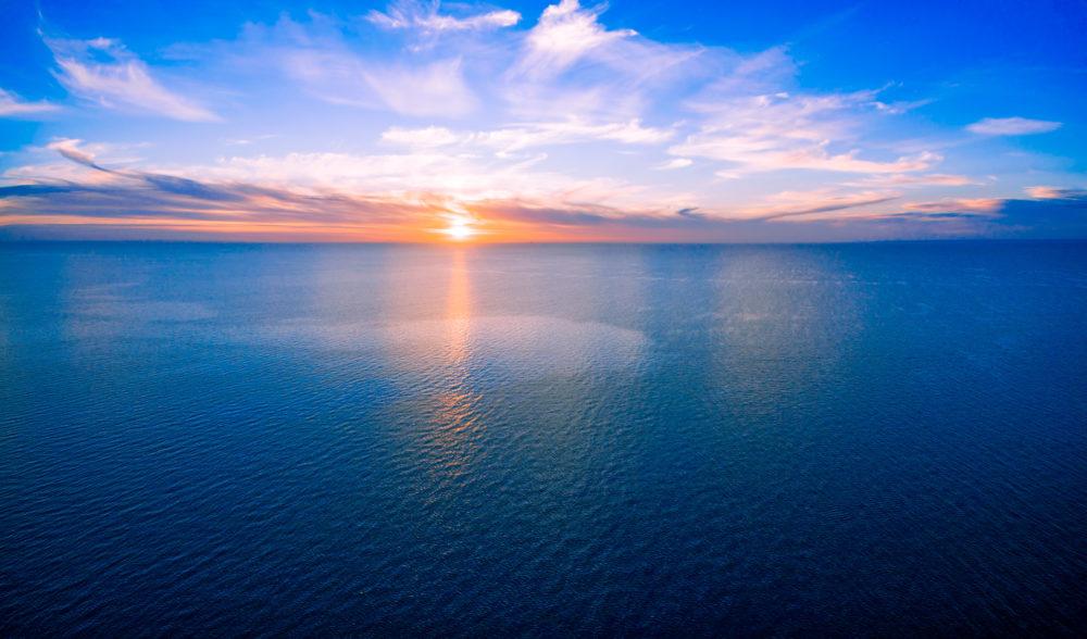 Sun setting over ocean - minimalist sunset aerial panorama