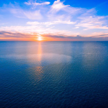 Sun setting over ocean - minimalist sunset aerial panorama