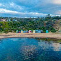 Colorful beach boxes reflecting in the ocean at Ranelagh beach. Mornington Peninsula, Victoria, Australia
