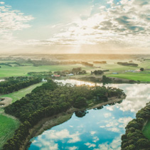 Wide aerial panorama of sunset over Hopkins River and grasslands in Warrnambool, Australia