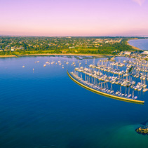 Aerial panorama of Melbourne coastline and marina with moored yachts at pink sunset. Beautiful vivid colors.