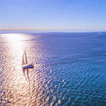 Lonely sailboat in wast waters backlit by the sun - aerial view