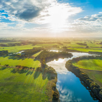 Sunset over river in rural area - aerial view