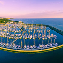 Aerial panoramic view of moored sailboats, breakwater, and Melbourne coastline at beautiful sunset