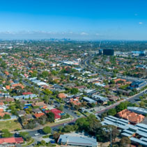 Wide aerial panorama of Oakleigh suburb with Melbourne CBD high rise buildings in the distance