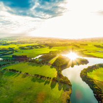 Bright sunset over scenic river in lush green countryside