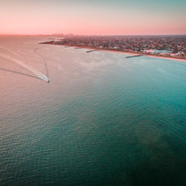 Aerial view of boat sailing across Port Phillip bay with Melbourne coastline and suburban areas in the background at beautiful sunset