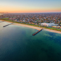 Aerial view of Port Phillip Bay and Melbourne coastline suburban living quarters at dusk