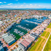 Luxurious suburban area near ocean with boats moored in private marina - aerial view