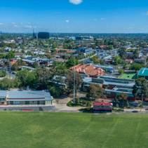 Aerial panorama of Melbourne suburbs and sports oval on bright sunny day