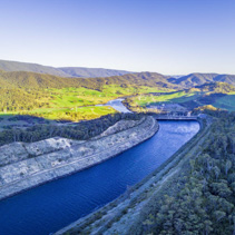 Aerial panorama of water canal leading to Tumut Power Station and beautiful hills at sunset. NSW, Australia