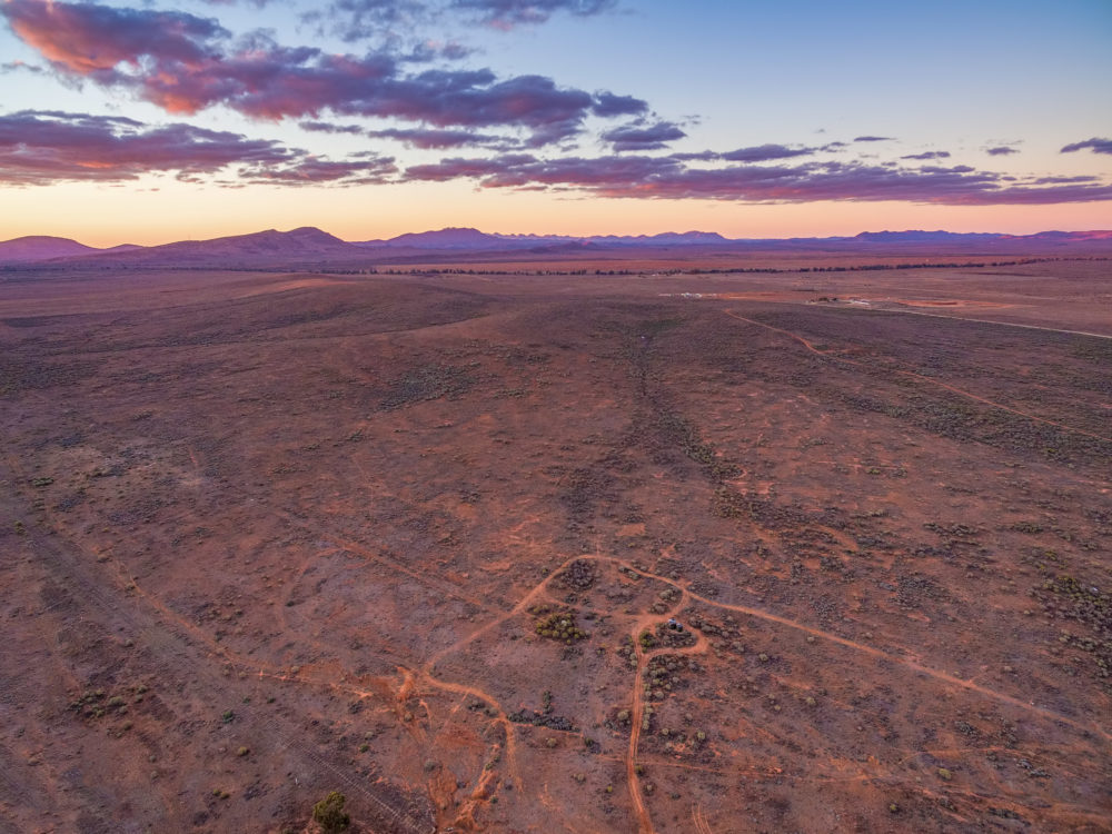 Desert land and Flinders Ranges peaks in the distance at dusk - aerial view